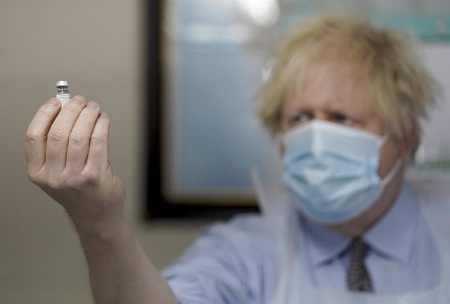 01 February 2021, United Kingdom, Batley: UK Prime Minister Boris Johnson holds a bottle of the Pfizer BioNTech vaccine during a visit to a coronavirus vaccination centre. Photo: Jon Super/PA Wire/dpa