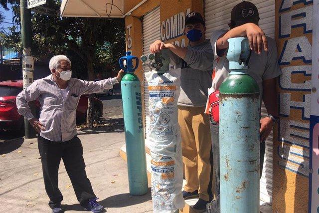 Mexicanos hacen cola para rellenar bombonas de oxígeno en la capital del país.