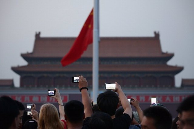 Chinese tourists watch the customary ceremony of lowering flag at Tiananmen Square on June 3, 2013 in Beijing, China.