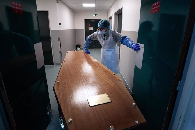 29 January 2021, France, Paris: A medical staff member at Bichat-Claude Bernard Hospital slides a casket into a mourning room in preparation for the family to say goodbye to their loved one. Photo: Joel Saget/AFP/dpa