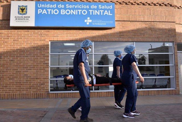 Cuatro sanitarios llevan en camilla a un paciente en Bogotá durante un ensayo de cara al comienzo de las vacunaciones contra el coronavirus en el país, que empezarán el próximo 20 de febrero.