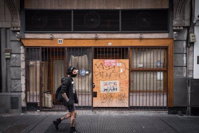Un joven pasea al lado de un comercio tapiado en una de las principales calles de Buenos Aires.