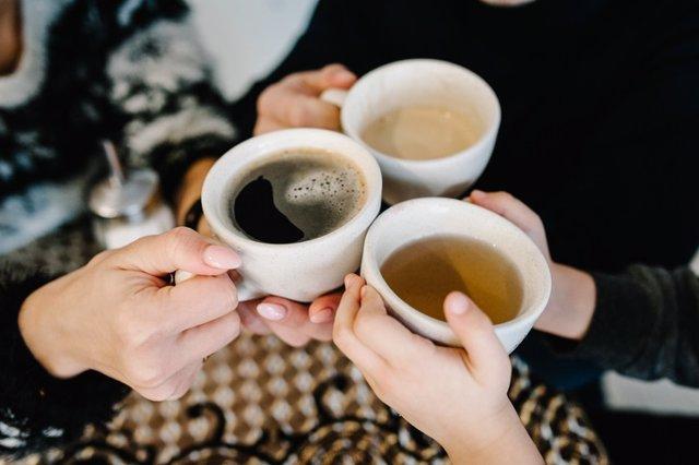 Manos de personas con tazas de té y café.