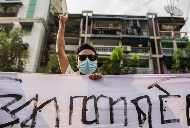 05 February 2021, Myanmar, Yangon: A protester flashes the three fingers salute while holding a banner during the demonstration against the military coup in Myanmar. Myanmar's military seized power on 1 February 2021 and detained government officials incl