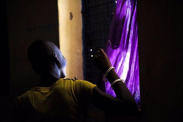 Una mujer mira por la ventana durante el confinamiento en el centro de estancia temporal de Kalas, en Uganda