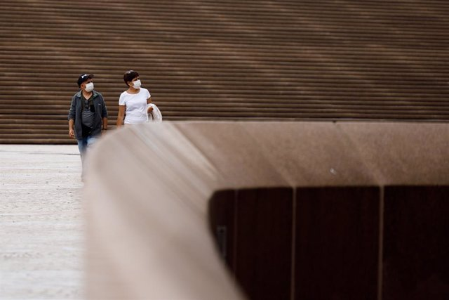 A couple wearing face masks in Sydney, Sunday, January 3, 2021. Mandatory mask restrictions are in place for many venues across greater Sydney as NSW works to contain COVID-19 outbreaks while avoiding harsh lockdown measures. (AAP Image/Paul Braven) NO AR