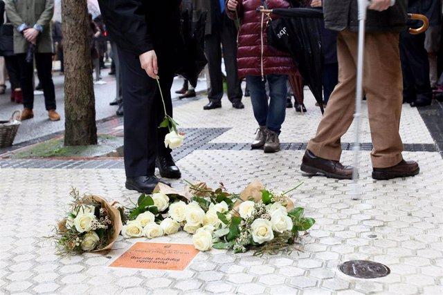 Una persona coloca una flor ante la placa conmemorativa de Fernando Múgica Herzog en San Sebastián, Euskadi (España), a 6 de febrero de 2021. El Ayuntamiento de San Sebastián ha colocado este sábado una placa en memoria del abogado e histórico militante s