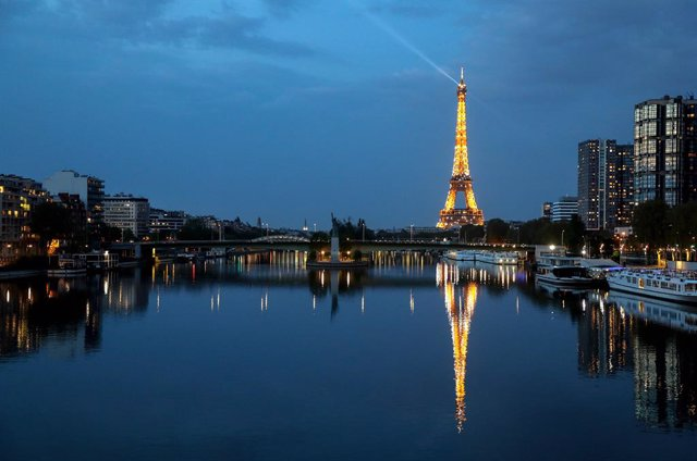 12 April 2020, France, Paris: The Eiffel Tower is reflected on the Seine river. Photo: Ludovic Marin/AFP/dpa