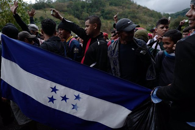 16 January 2019, Guatemala, Aguas Calientes: Migrants from Honduras hold their identity cards high as they reach the Aguas Calientes border crossing between Honduras and Guatemala, as they take their way to the north, plans to immigrate to the USA during