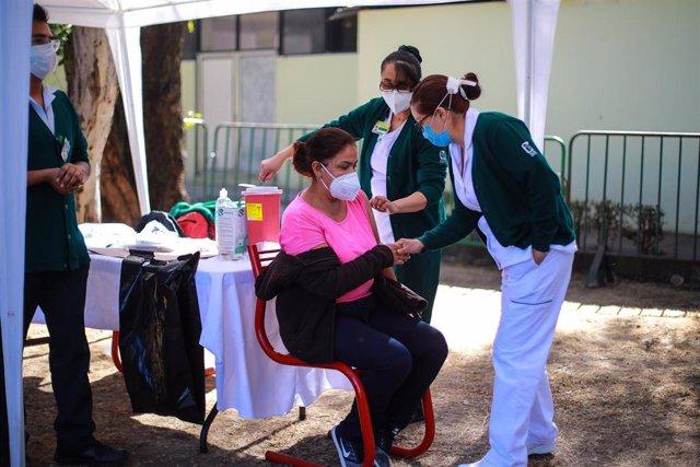Una sanitaria recibe la vacuna en México.