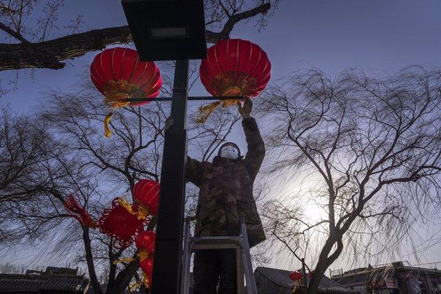 Un trabajador cuelga un farolillo en Pekín como parte de la decoración del festival de primavera.