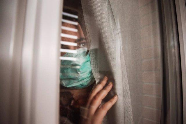 Mujer con mascarilla mira con miedo por la ventana.