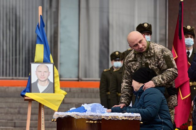 14 January 2021, Ukraine, Zaporizhzhia: People pay their respects to perished soldier Oleh Andriienko during his funeral ceremony outside the Zaporizhzhia Regional State Administration. The 37-year-old serviceman was shot dead by a sniper near the Pisky v