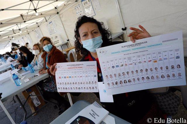Una mujer procedente de Ecuador posa con todos los candidatos a la presidencia de la República de Ecuador, en una de las 64 mesas electorales repartidas por varias poblaciones de la Región de Murcia, en el Auditorio de Centro y Congresos de Murcia (España