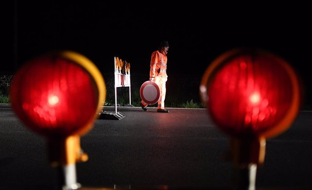 """15 May 2020, Bavaria, Griesen: An employee of the road maintenance department removes a """"no entry"""" traffic sign at the Griesen border crossing and carries it to the car. At midnight, many borders with neighbouring Austria were reopened  after a two-month"""