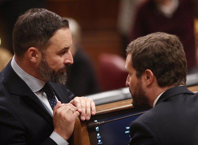 El presidente de VOX, Santiago Abascal (izq) y el presidente del PP, Pablo Casado (dech), hablan durante la sesión de constitución de las Cortes para la XIV Legislatura en el Congreso de los Diputados, Madrid (España), a 3 de diciembre de 2019.