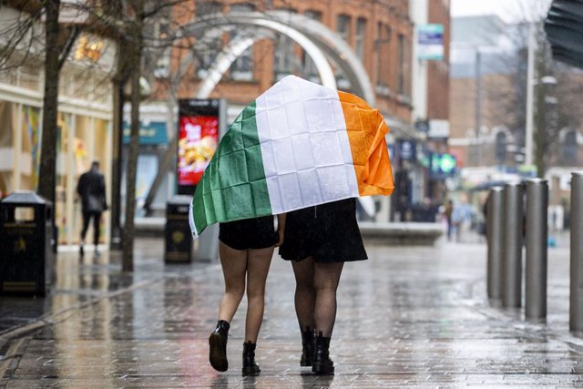 17 March 2020, Northern Ireland, Belfast: Two young girls shelter under the Irish flag as they walk through Belfast on St Patrick's Day. Due to Coronavirus Belfast City Council cancelled the festivities for the safety of the general public. Photo: Liam Mc