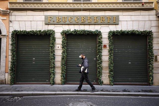 24 December 2020, Italy, Rome: A man walks past closed shops in Via Condotti street amid the Coronavirus lockdown during Christmas. Photo: Cecilia Fabiano/LaPresse via ZUMA Press/dpa