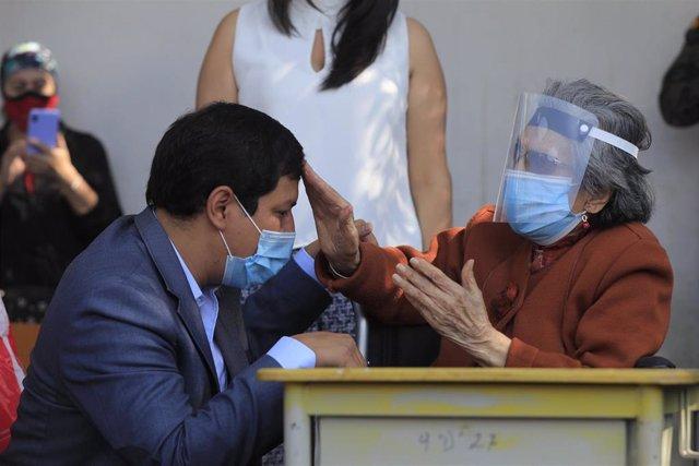 El candidato presidencial ecuatoriano Andrés Arauz con su abuela de 106 años en un centro de votación de Quito