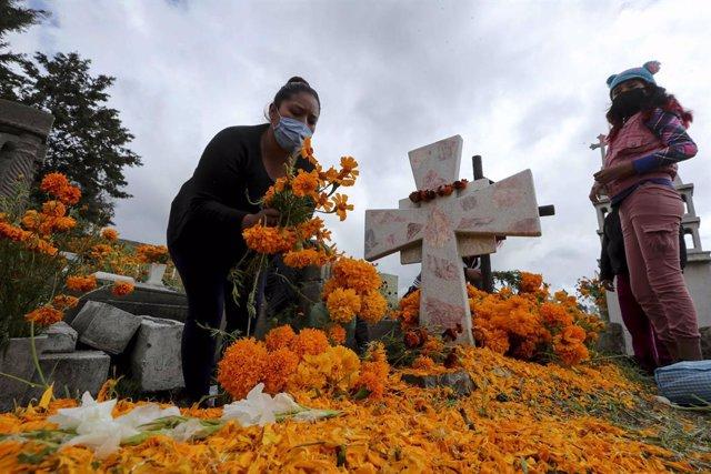 Una persona deposita una ofrenda floral en la tumba de un familiar fallecido a causa de la COVID-19.