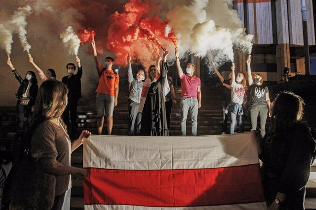 26 August 2020, Ukraine, Kiev: Members of the Belarusian community in Ukraine and Ukrainian activists burn red and white smoke bombs and wave the flag of the Rada of the Belarusian Democratic Republic (the Belarusian opposition flag) during rally in solid