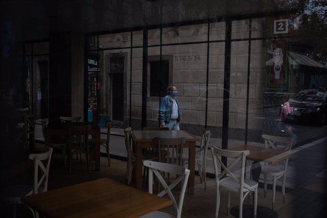 Un home camina pel carrer davant d'una cafeteria a Barcelona. Foto d'arxiu.
