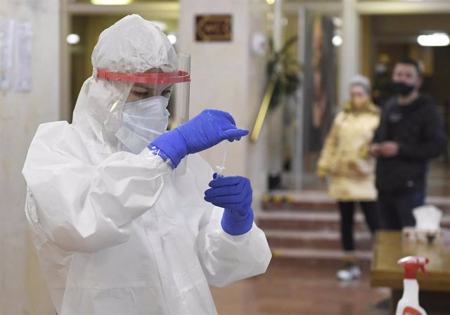 03 February 2021, Slovakia, Kosice: A nurse in a protective suit cheks a swab during antigen testing at the collection point at the Koicky hospital. Photo: Franti?ek Iván/TASR/dpa