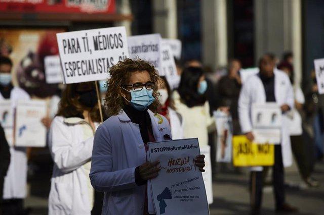 Una trabajadora sanitaria sostiene un cartel durante una concentración convocada por la Asociación de Médicos y Titulados Superiores de Madrid (AMYTS), en la Puerta del Sol.