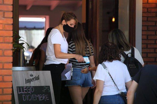 La trabajadora de un restaurante de Buenos Aires, toma la temperatura a sus clientes antes de su ingreso al establecimiento.