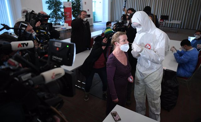 03 February 2021, Austria, Vienna: A health worker takes a swab from a woman for Coronavirus test at the new Corona test centre near Schoenbrunn Palace. Photo: Helmut Fohringer/APA/dpa