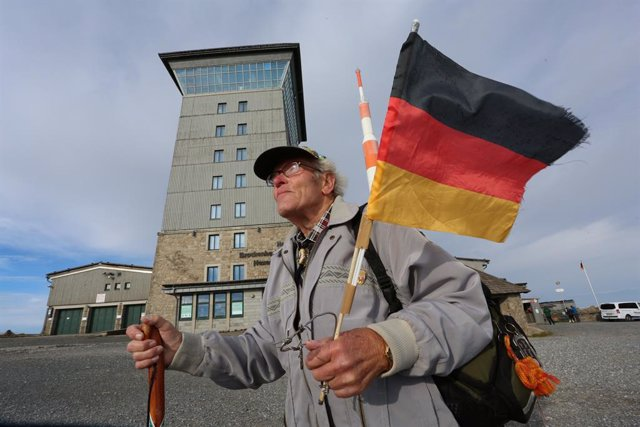 03 October 2020, Saxony-Anhalt, Schierke: Record hiker Benno Schmidt holds a national flag as he hikes to the Brocken during the German Unity Day. Photo: Matthias Bein/dpa-Zentralbild/dpa