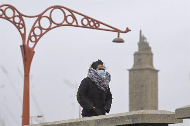 Una persona camina protegida del frío en el Paseo Marítimo, el mismo día del paso de la borrasca Justine convertida en ciclogénesis explosiva en A Coruña, Galicia (España), a 31 de enero de 2021. Justine dejó ayer, 30 de enero rachas superiores a los 120