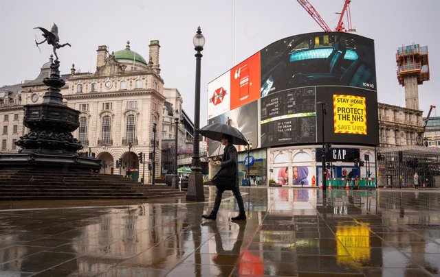 29 January 2021, United Kingdom, London: A man with an umbrella walks past a government coronavirus advert on the big screen at Piccadilly Circus during England's third national lockdown to curb the spread of coronavirus. Photo: Dominic Lipinski/PA Wire/d