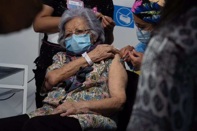 03 February 2021, Chile, Santiago: Leonila Gonzalez, 96, receives a dose of the Sinovac Coronavirus vaccine by a health personnel on the first day of mass vaccination, at a vaccination centre mounted at the Bicentenario Stadium. Photo: Matias Basualdo/ZUM