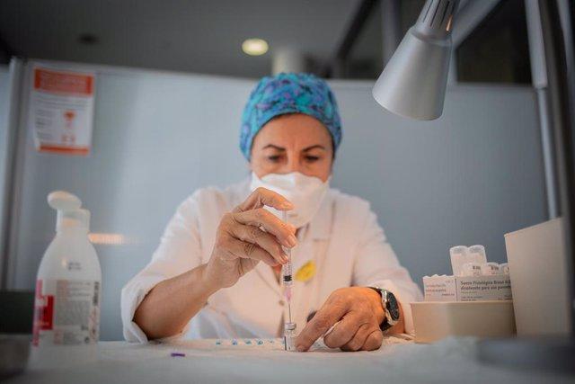 Una enfermera prepara la vacuna Pfizer-BioNtech contra el COVID-19 antes de administrársela a un profesional sanitario en el Hospital de la Santa Creu i Sant Pau de Barcelona, Catalunya (España), a 14 de enero de 2021