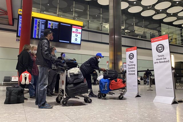 18 January 2021, United Kingdom, London: Passengers wait in a line outside the testing centre in the arrival hall of Terminal 5 at London's Heathrow Airport, passengers arriving from anywhere outside the UK must have proof of a negative coronavirus test a