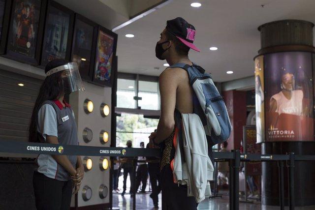 Un hombre con mascarilla hablando con la trabajadora de un cine en Venezuela