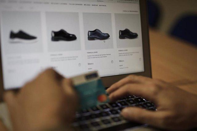Una persona se dispone a pagar con su tarjeta de crédito una compra online realizada con su ordenador en la página de un comercio