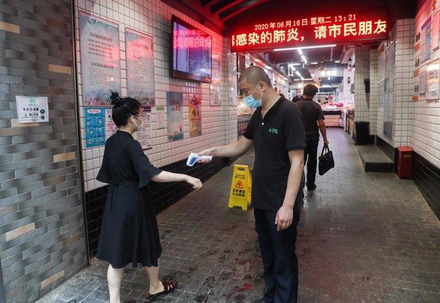 Una mujer se somete a una prueba de temperatura antes de poder entrar a un mercado de verduras en Shanghái, en el este de China.