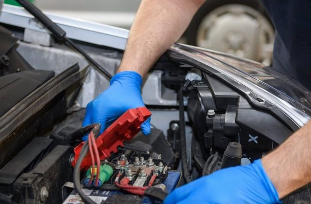 Imagen de un operario manipulando una batería de un coche.