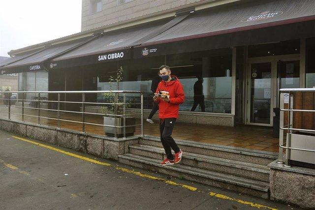Un joven recoge un café de un establecimiento abierto en San Cibrao das Viñas, en Ourense, el pasado mes de noviembre.