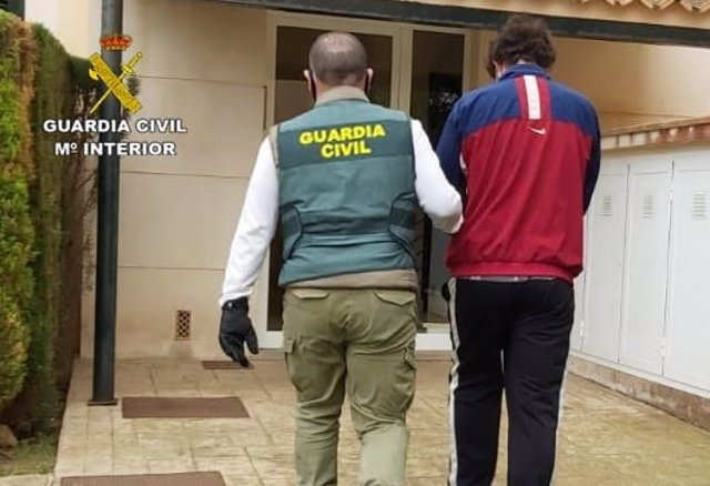 Un agente de la Guardia Civil con el joven detenido en Llucmajor por varios robos en vehículos.
