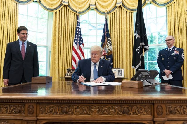 HANDOUT - 15 May 2020, US, Washington: US President Donald Trump (C), joined by US Department of DefenCe Secretary Mark Esper (L) and US Space Force Senior Enlisted Advisor CMSgt Roger Towberman, signs an Armed Forces Day Proclamation at the Oval Office o