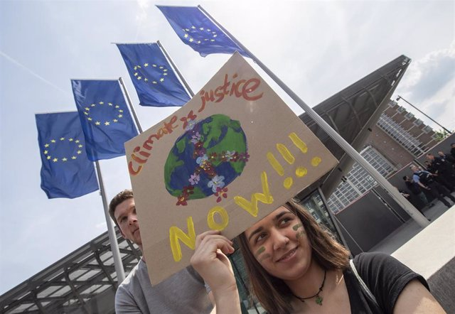 """24 May 2019, Frankfurt am Main: A woman holds a sign with the inscription """"Climate Justice Now"""" in front of the European Central Bank (ECB) during the Fridays for Future - climate strikes for the implementation of the Paris World Climate Agreement."""