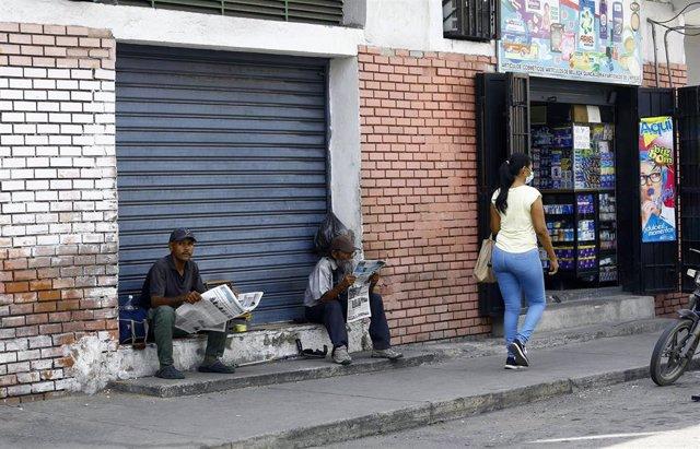 Un grupo de personas lee el periódico en Venezuela.