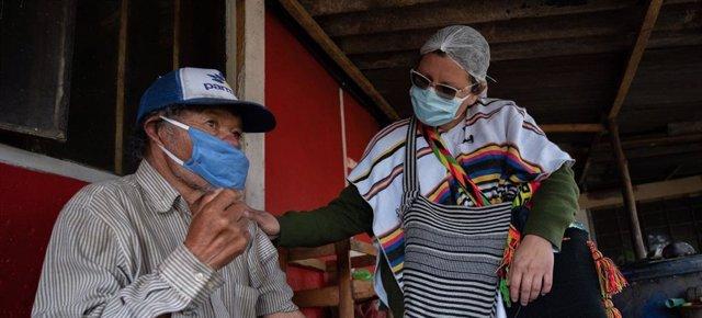 Una enfermera revisa a un hombre de origen indígenas en Suba, Bogotá, durante la pandemia de COVID-19.
