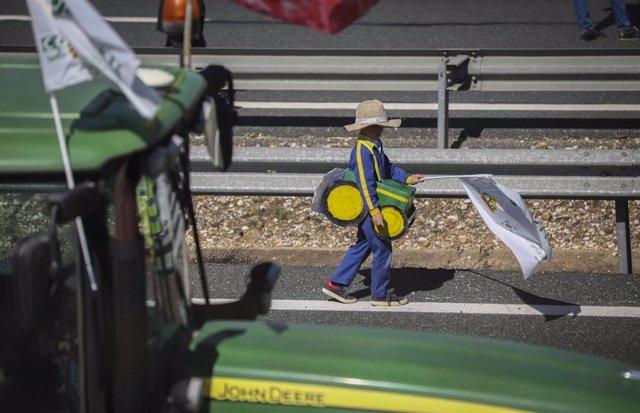 Un niño con un disfraz de tractor durante la manifestación que ha cortado la A-4 en Carmona durante la tractorada organizada por agricultores en Sevilla, a 25 de febrero de 2020.