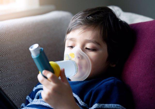 Niño con asma. Inhalador con cámara.