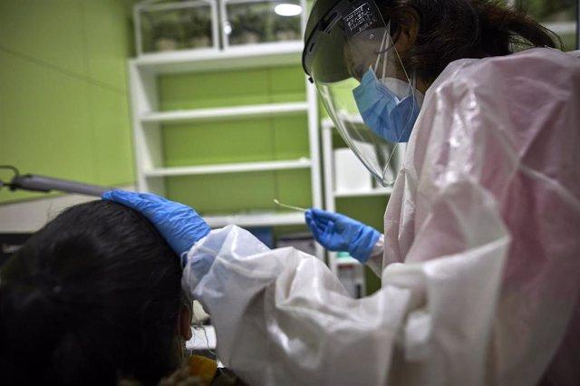 Una farmacéutica se dispone a realizar un test de antígenos a una mujer en la Farmacia Las Gemelas en Madrid (España), a 11 de febrero de 2021. El pasado miércoles 3 de febrero, Salud Pública comenzó a mandar SMS para que los ciudadanos asintomáticos que