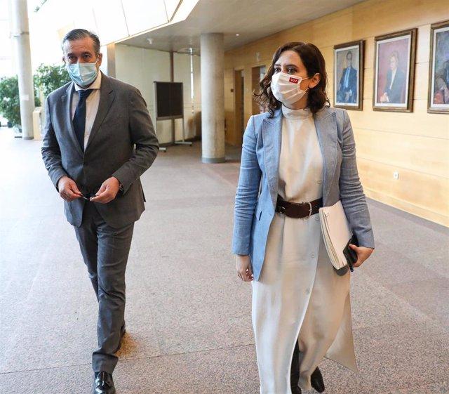 La presidenta de la Comunidad de Madrid, Isabel Díaz Ayuso (d), y el consejero de Justicia, Interior y Víctimas, Enrique López (i), antes de una sesión plenaria celebrada en la Asamblea de Madrid, en Madrid, (España), a 11 de febrero de 2021.